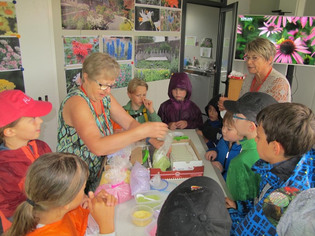 Kinder füllen den mit verschiedenen Blüten gefärbten Zucker in kleine Glasfläschchen, die sie als Andenken mit nach Hause nehmen dürfen